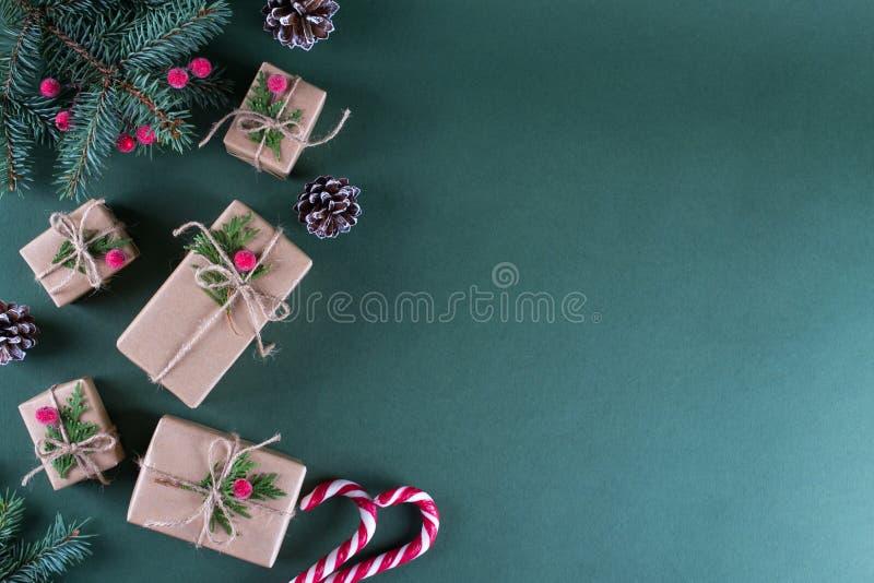 La Navidad Regalos del embalaje en papel beige del arte del vintage y la decoración natural Ramas del abeto y de la baya roja Vis imagen de archivo libre de regalías