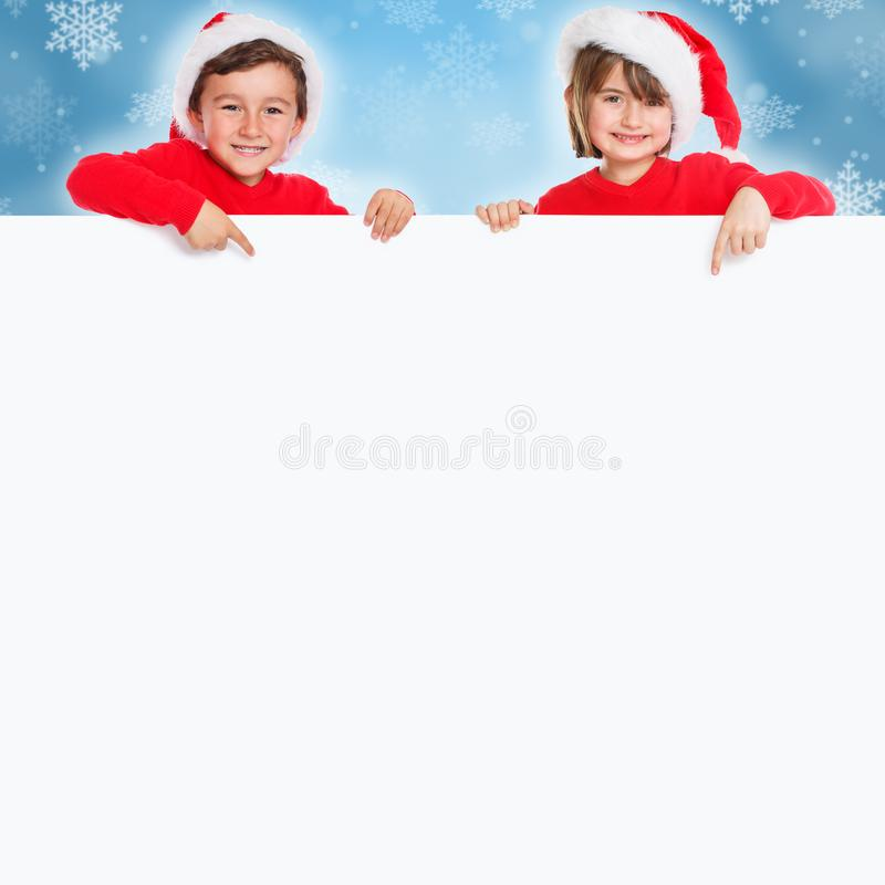 La Navidad Santa Claus del muchacho de la muchacha de los niños de los niños que señala el espacio vacío feliz de la copia del co foto de archivo