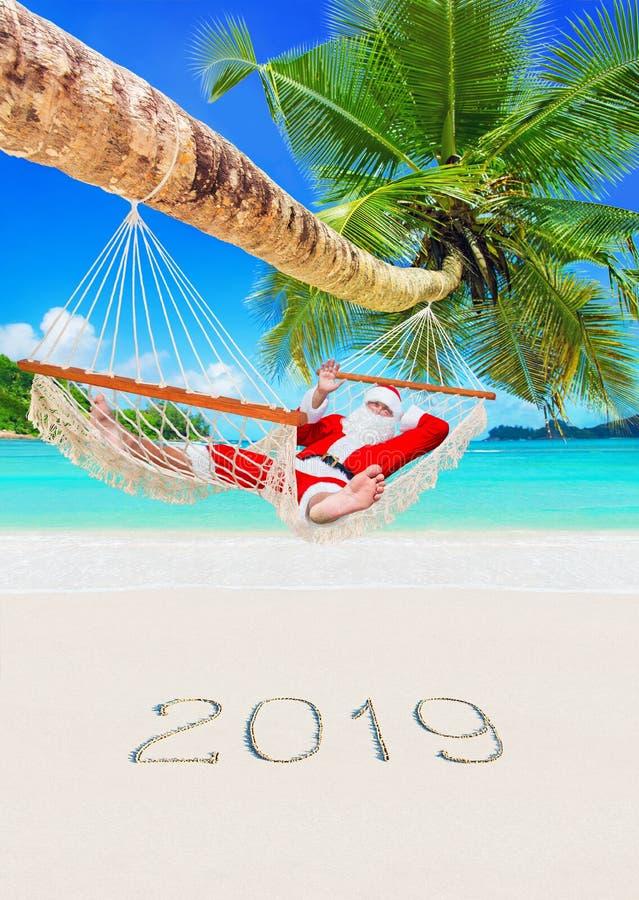 La Navidad Santa Claus se relaja en hamaca debajo de la palma en la playa arenosa tropical, estación de la Feliz Año Nuevo 2019 foto de archivo libre de regalías