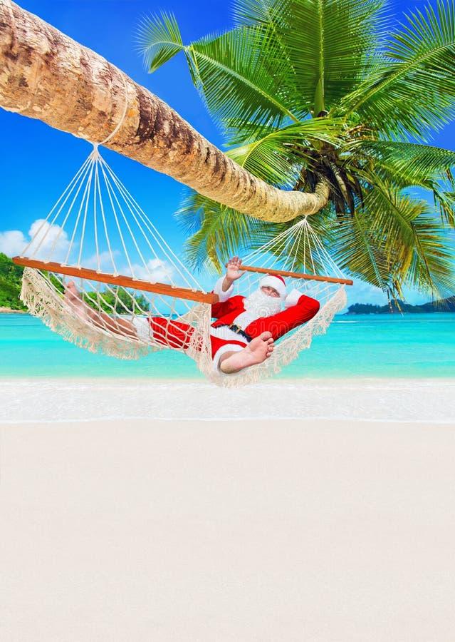 La Navidad Santa Claus se relaja en hamaca debajo de la palmera en la playa arenosa tropical del océano fotos de archivo libres de regalías