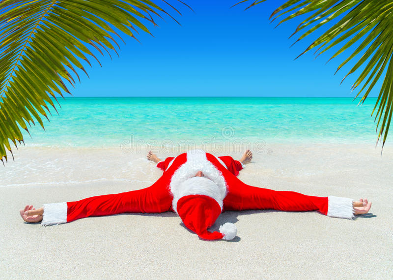 La Navidad Santa Claus toma el sol en la playa arenosa de la palma tropical del océano imagenes de archivo