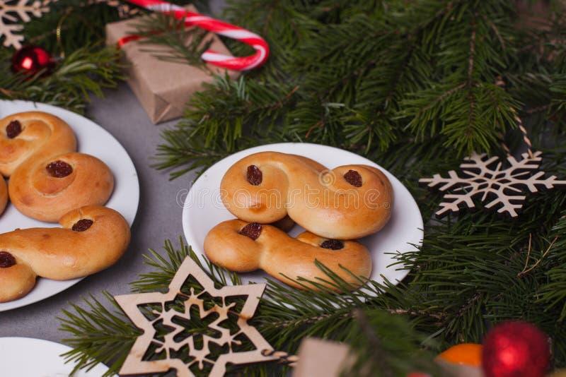 La Navidad sueca Los bollos suecos tradicionales en la torta se colocan en el ajuste de la Navidad Un bollo del azafrán, en lusse fotos de archivo libres de regalías