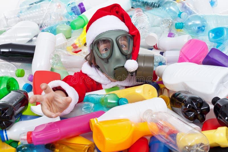 La Navidad tóxica - santa que se ahoga en botellas plásticas fotografía de archivo libre de regalías