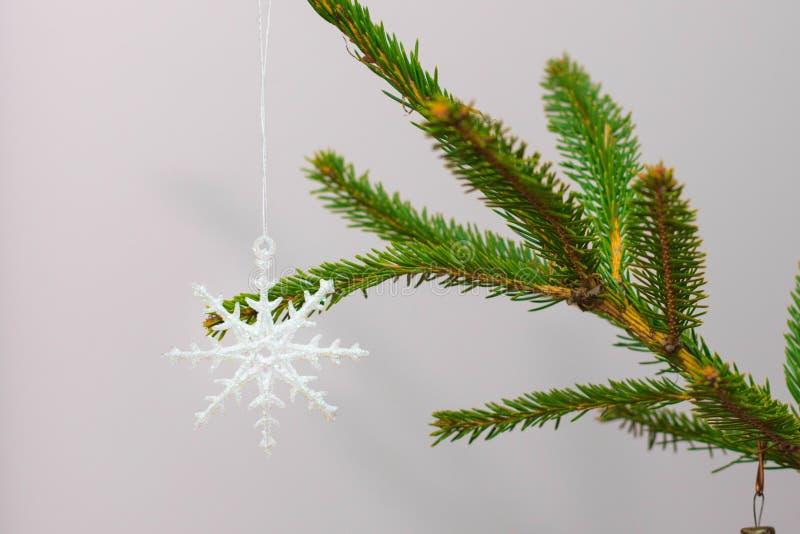 La Navidad tradicional o el Año Nuevo adornó el árbol con un juguete de plata del copo de nieve imagen de archivo