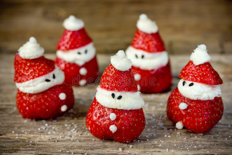 La Navidad trata para los niños - santa divertido poner crema azotado fresa fotos de archivo