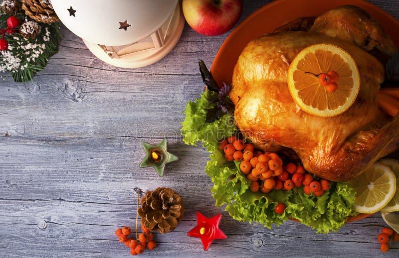 La Navidad Turquía con las bayas, los conos y las verduras en fondo de madera foto de archivo