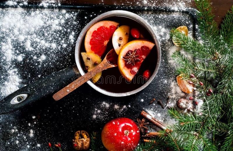 La Navidad Vino reflexionado sobre caliente con los ingredientes en cucharón auténtica encendido en fondo oxidado del metal del v imágenes de archivo libres de regalías