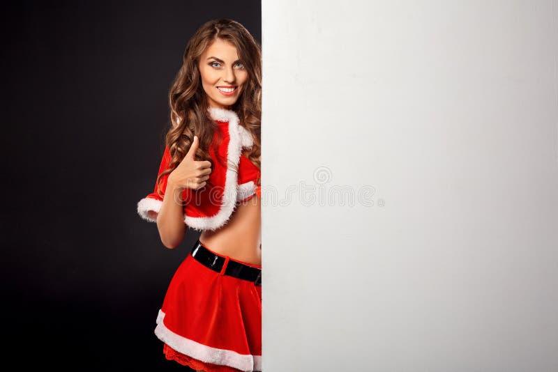 La Navidad y Año Nuevo Mujer en la situación del traje de santa aislada en negro con el pulgar de la demostración del tablero bla fotografía de archivo libre de regalías