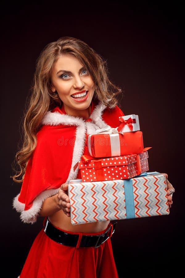 La Navidad y Año Nuevo Mujer en la situación del traje de santa aislada en negro con los presentes que miran la cámara sorprendid imágenes de archivo libres de regalías