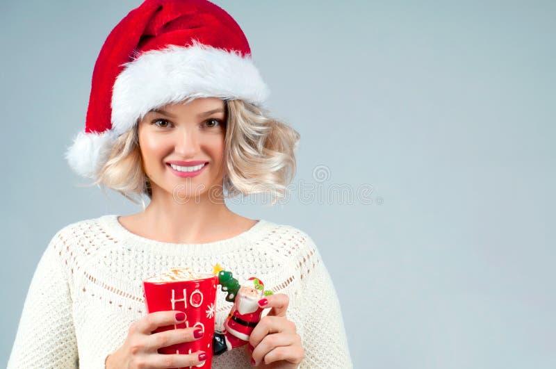 La Navidad y Año Nuevo La mujer en sombrero del ` s de santa está sosteniendo una taza de café foto de archivo