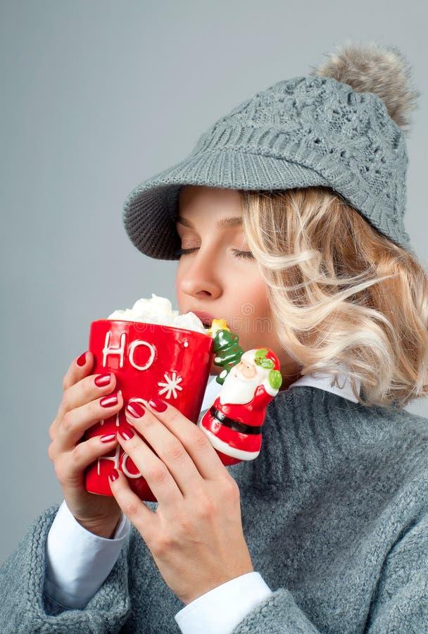 La Navidad y Año Nuevo La mujer en sombrero hecho punto está bebiendo el café fotos de archivo libres de regalías