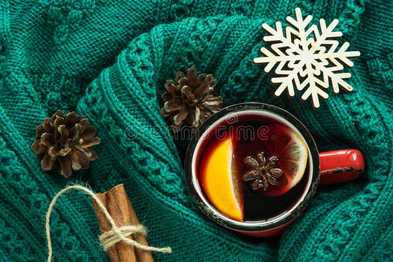 La Navidad y bebida caliente tradicional del invierno Vino reflexionado sobre en taza roja con la especia envuelta en suéter verd fotos de archivo
