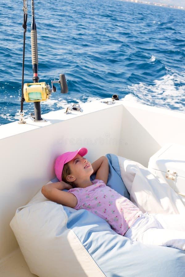 La navigation de fille d'enfant a détendu sur le paquet de bateau ejoying un petit somme image libre de droits