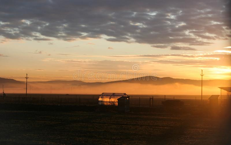 La nebbia nella valle ed in una serra è illuminata dal sole sopra le montagne immagine stock libera da diritti