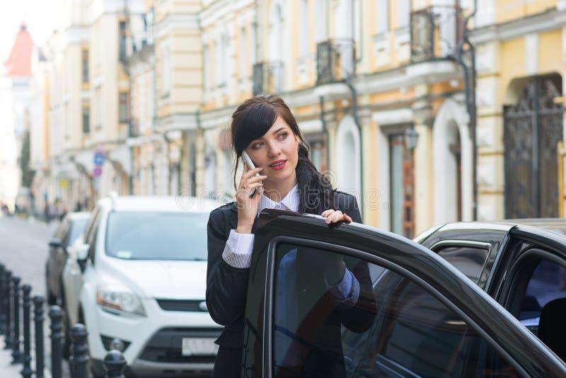 la Negocio-mujer consigue en el coche y habla en el teléfono celular imagen de archivo