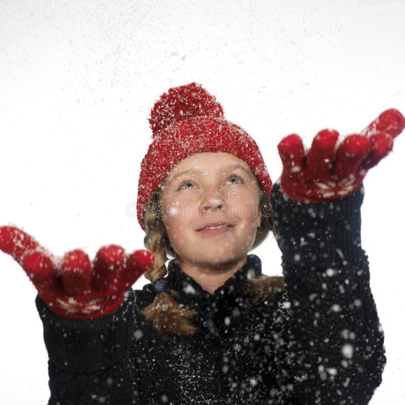 La neige contagieuse de fille heureuse s'écaille dans sa main photo libre de droits