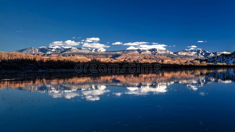 La neige a couvert des montagnes de sel de La et leurs réflexions dans le fleuve Colorado en hiver images stock