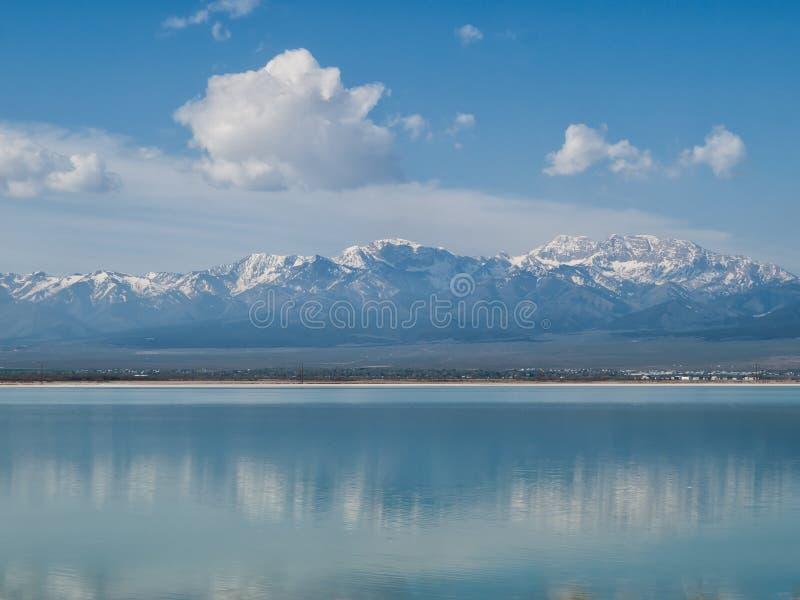 La neige a couvert des montagnes reflétées dans le lac bleu image libre de droits