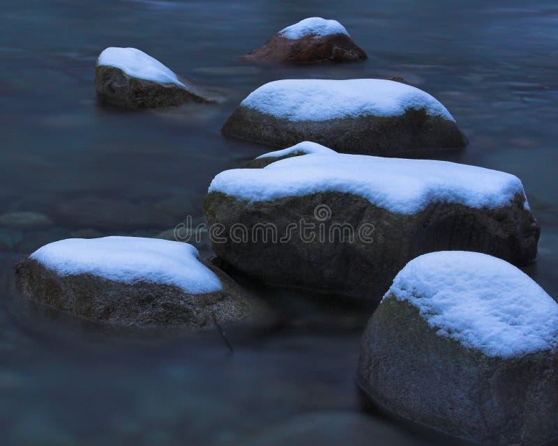 La neige a couvert des roches de fleuve photo libre de droits