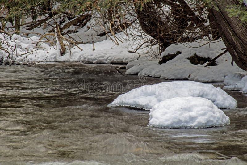 La neige a couvert des roches sur la rivière images libres de droits