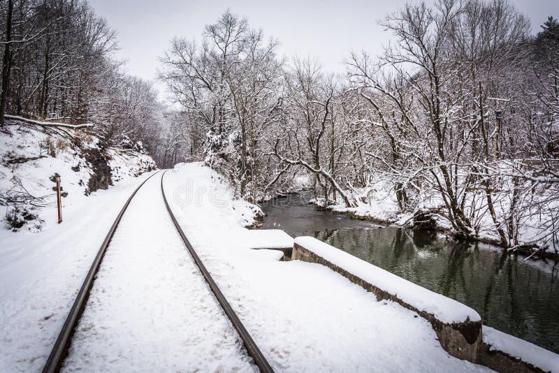 La neige a couvert des voies ferrées et une crique dans Carroll County rurale images stock