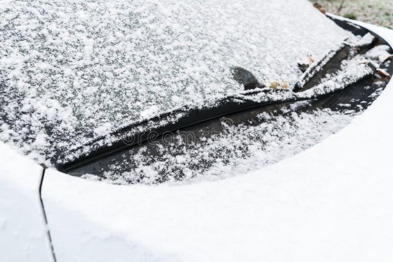 La neige a couvert la fenêtre de voiture d'essuie-glace, macro, fin  Les balais d'essuie-glace de voiture nettoient la neige des  photo libre de droits