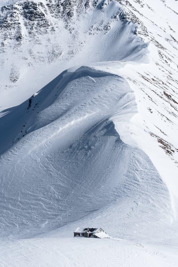 La neige a couvert l'arête de montagne menant vers le bas à la hutte alpine photos stock