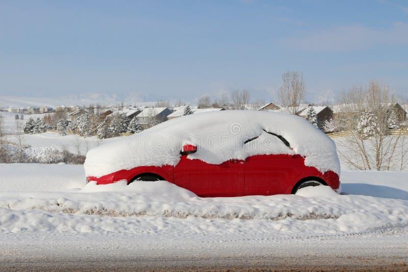 La neige a couvert la voiture rouge photo stock