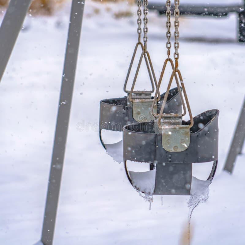 La neige a couvert le terrain de jeu d'oscillations de bébé en Utah photos libres de droits