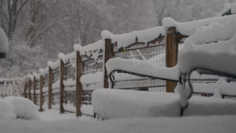 La neige a couvert les meubles de patio et la barrière de jardin photo stock