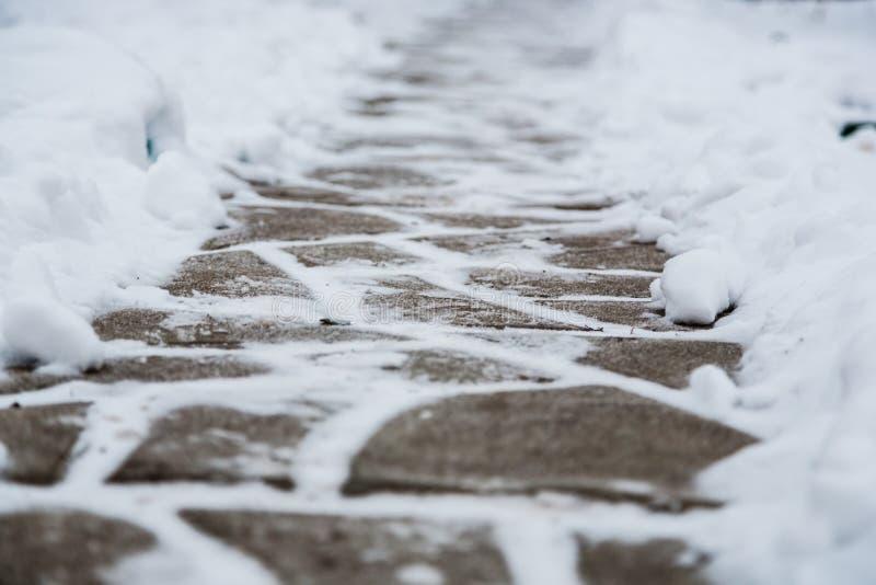 La neige a couvert les petites tuiles de pavage, les dalles après des chutes de neige Fond de trottoir d'hiver Utilisation pour l images libres de droits