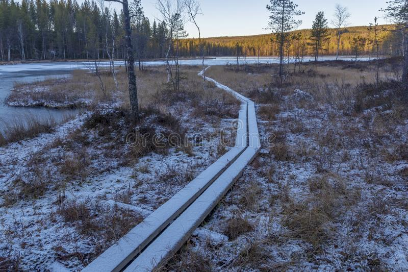 La neige a couvert la traînée de planche au-dessus d'un fatras menant à un lac d'IC photographie stock