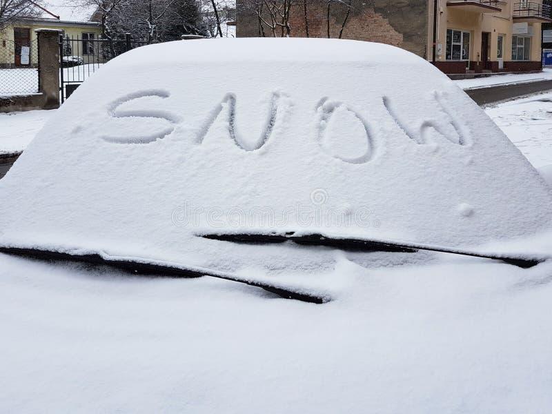 La neige de mot écrite sur une fenêtre de voiture couverte de neige voitures couvertes de neige pendant l'hiver Temps froid Circu photos libres de droits