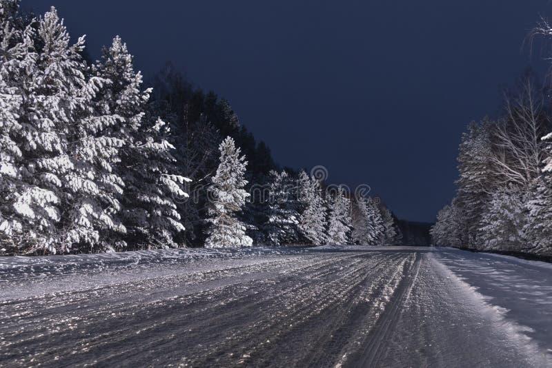 La neige de nuit a couvert la route non épluchée d'hiver photographie stock libre de droits