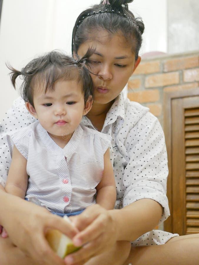 La neonata asiatica che esamina il suo ` s della madre passa la frutta della sbucciatura, pomelo fotografia stock