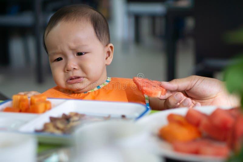 La neonata asiatica di mese sveglio 5-6 non vuole mangiare l'anguria fotografia stock libera da diritti