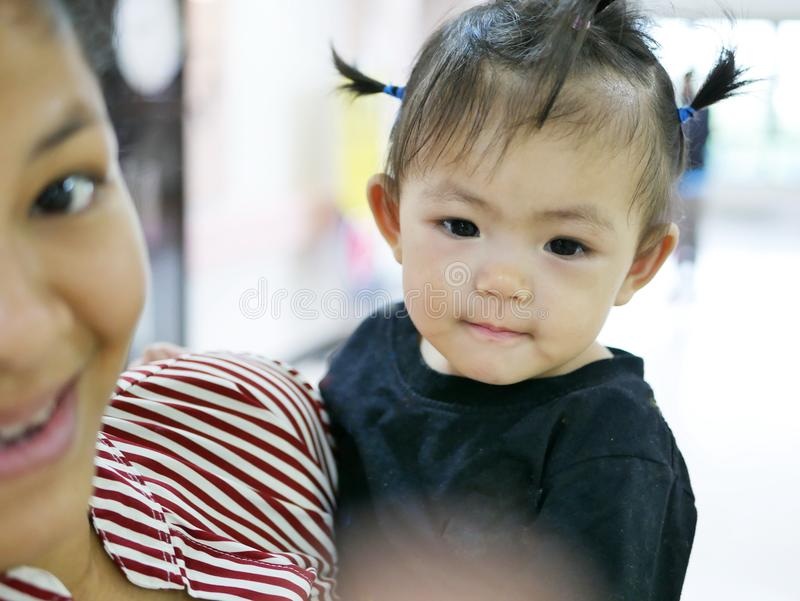 La neonata asiatica gode di di prendere la foto, esaminando il punto in cui sua madre che la indica e che guida per esaminare immagini stock