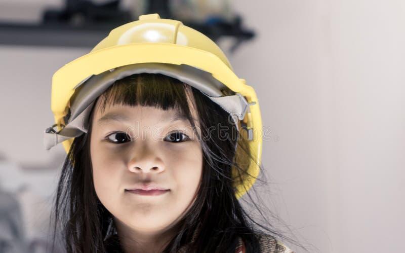 La neonata asiatica sta portando il cappello di ingegneria fotografia stock