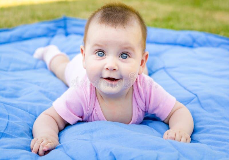 La neonata piccola sveglia è sorridente e giocante sull'erba fotografia stock libera da diritti