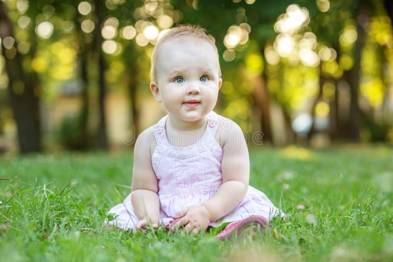 La neonata si siede nell'erba in suo vestito 1 anno Il concep fotografia stock libera da diritti