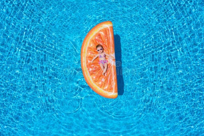 La neonata sta trovandosi su un galleggiante a forma di della fetta arancio sopra l'acqua blu dello stagno fotografie stock libere da diritti