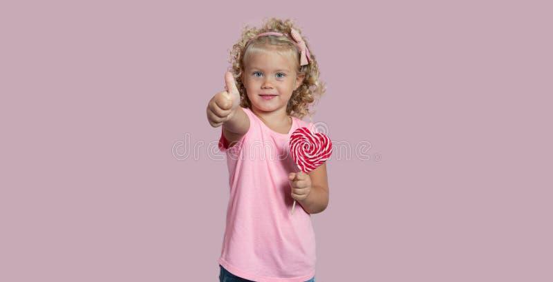 La neonata sveglia che tiene una lecca-lecca sorride e mostra il pollice su isolato sopra fondo rosa fotografia stock