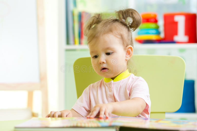 La neonata sveglia legge un libro a casa fotografia stock libera da diritti