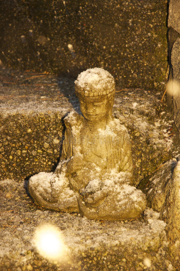 La neve che cade alla notte sulla statua di Buddha cattura la presenza in un fiocco di neve immagini stock