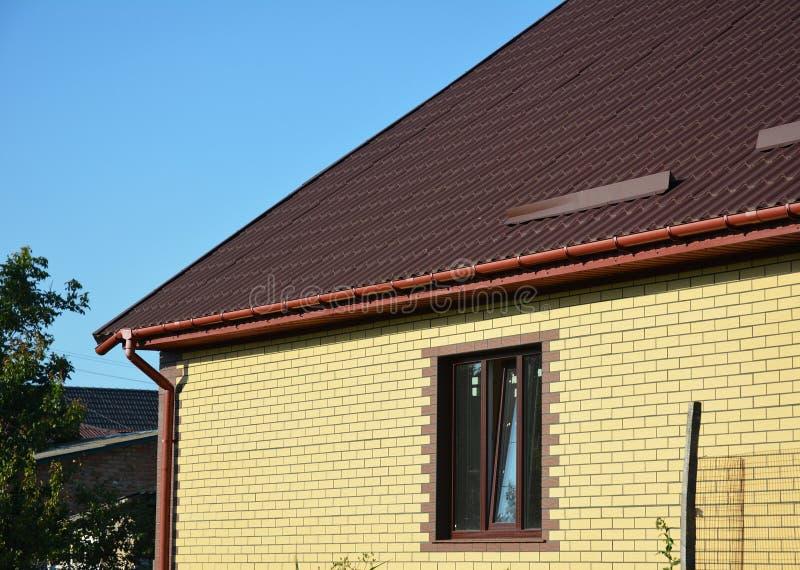 La neve del tetto custodice con la nuova grondaia di plastica della pioggia Le guardie della neve del tetto del metallo impedisco fotografia stock libera da diritti