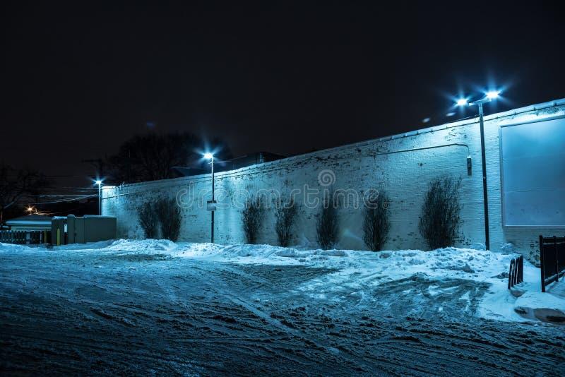La neve ha riempito il parcheggio scuro della città alla notte immagini stock libere da diritti