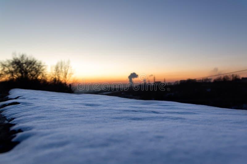 La neve luminosa si trova sulla terra, accesa dal tramonto, che illumina il fumo dal camino fotografia stock