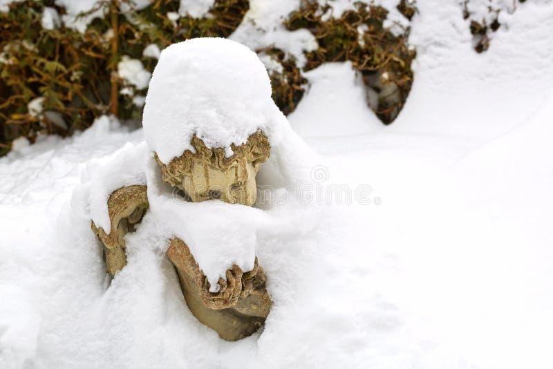 La neve si sfalda, cristalli di ghiaccio che si formano sulla scultura di pietra sveglia di angelo fotografie stock libere da diritti