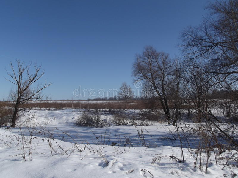 La neve su uno stagno congelato è coperta dalle ombre blu immagini stock