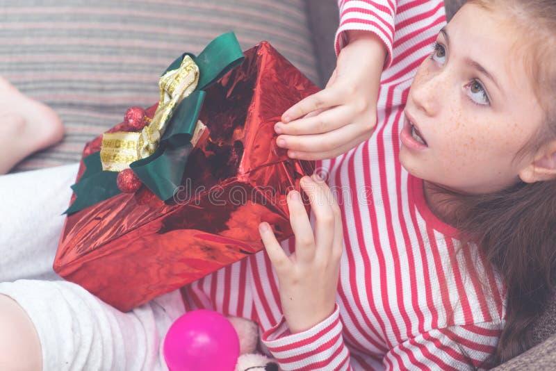 La niña abre la caja del regalo de Navidad fotografía de archivo libre de regalías